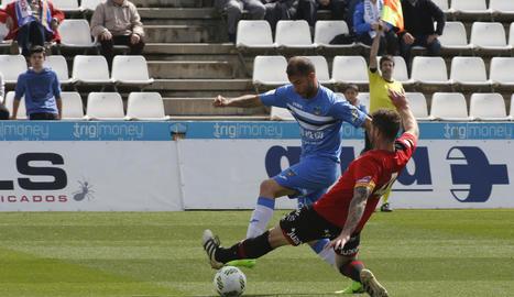 Cristian Gómez, que va entrar a la segona meitat, intenta anar-se'n del capità visitant Raúl.