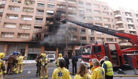 Bombers treballen a l'immoble afectat per les flames i el fum.