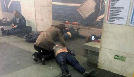 Una dona intenta socórrer una de les víctimes del brutal atemptat al metro.
