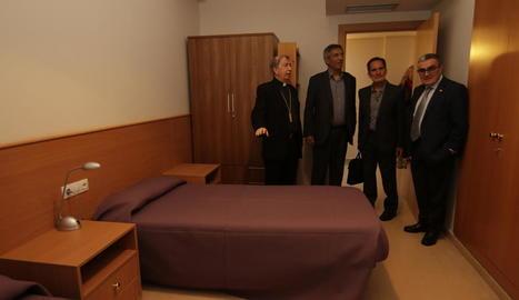 El bisbe, els responsables de Sant Joan de Déu i Àngel Ros, ahir en una de les habitacions del centre.
