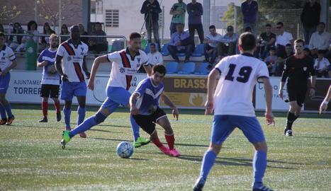 Un jugador del Solsona mira de mantenir el control de la pilota davant la presència de diversos rivals.