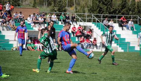 Un jugador del Térmens aconsegueix connectar amb la pilota, malgrat la pressió rival.