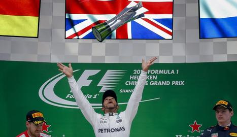 Lewis Hamilton llança a l'aire el trofeu per celebrar la victòria, flanquejat per Sebastian Vettel i Max Verstappen.