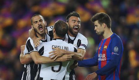 Piqué, capbaix, mentre diversos jugadors de la Juventus celebren la classificació.