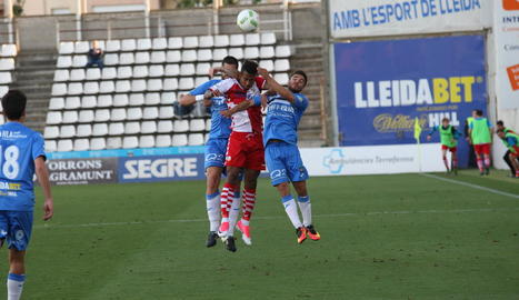Jordan Gaspar lluita per una pilota entre dos jugadors del Lleida en una acció del partit d'ahir.
