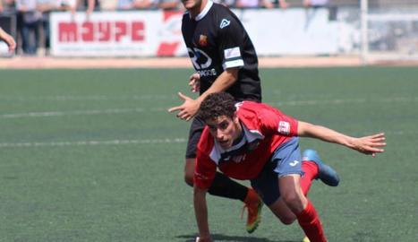El local Galcerán pugna amb un adversari pel control de la pilota, en una acció del partit.