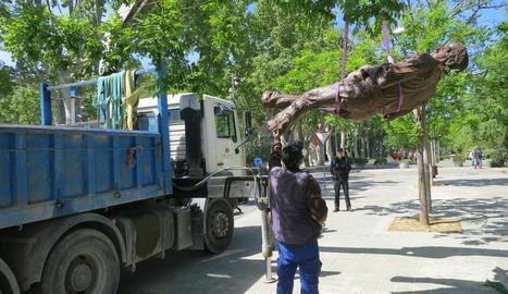 Un operari retira amb un camió grua l'estàtua, que va ser portada a un magatzem i serà restaurada.