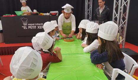 Nens i nenes van aprendre a cuinar a l'espai Petit Xef de Fira Q de Balaguer.