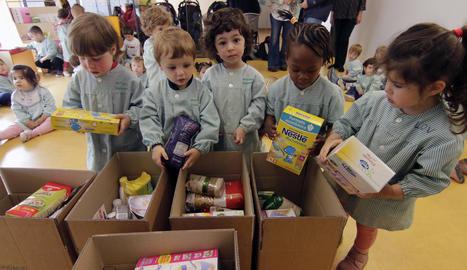 Els nens de l'escola bressol Parc de Gardeny, ahir dipositant aliments a les caixes de recollida.