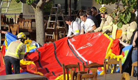 Diversos operaris i bombers retiren el castell unflable del restaurant Mas Oller.