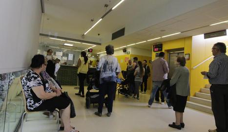 Usuaris del CAP Primer de Maig fent cua davant de la taula d'atenció, ahir al migdia durant la incidència.