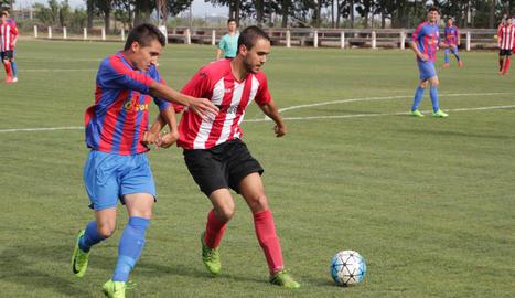 Un jugador del Térmens pugna la pilota a un altre del Puigvertenc, que defensa la possessió del cuir.