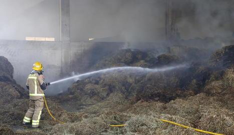 Un bomber apagant ahir l'incendi a l'interior de la granja.