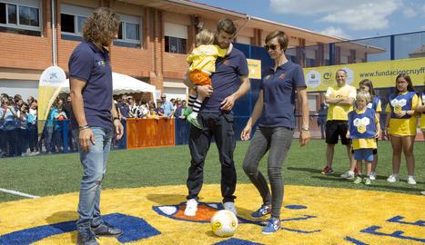 Piqué, Puyol, el directiu blaugrana Jordi Cardoner i la filla de Cruyff (esquerra), amb un grup de nens.