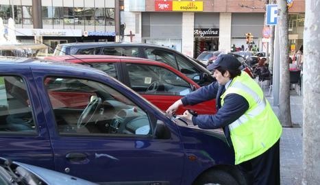 Una vigilant de zona blava posa una multa, en una imatge d'arxiu.