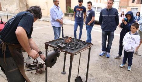 Visitants observen el treball d'un forjador en una mostra que va reunir més de trenta oficis.