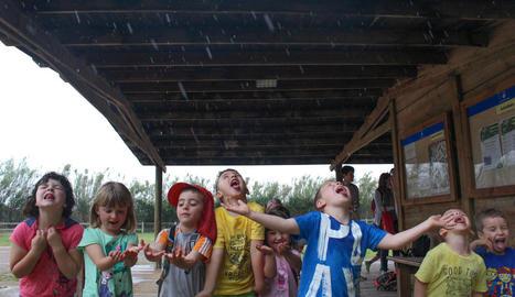 pluja. Alumnes de l'escola de Torà jugant amb la pluja sota els porxos de la zona de la Carbonera a la Mitjana.