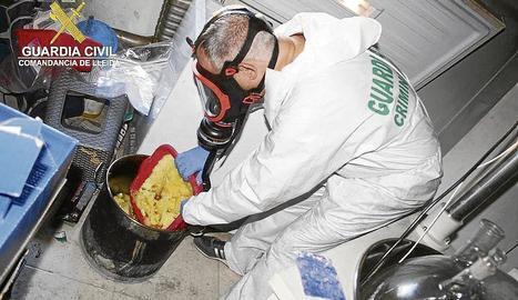 Un agent de la Guàrdia Civil amb part de la droga confiscada durant l'operació.
