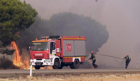 Imatge de dos bombers lluitant contra les flames.