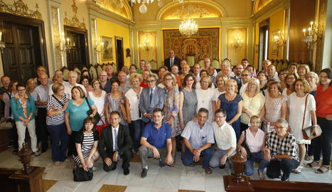 Foto de família de les autoritats amb els funcionaris de la Paeria homenatjats.