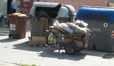 Un home buscant en un contenidor a Lleida.