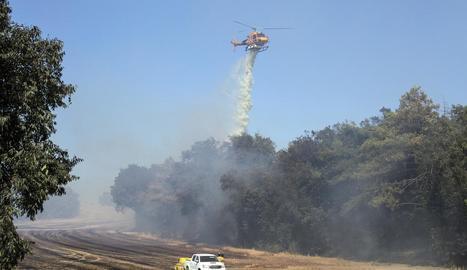 Un helicòpter llança aigua en l'incendi de Pujalt, a prop d'Estaràs.