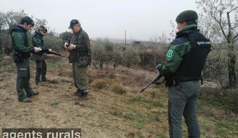 Un grup de tres agents rurals, amb armilles antibales i una carrabina en un control de caça.