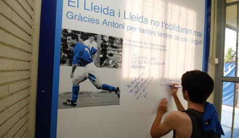 Un aficionat escriu un missatge de record al mural dedicat a Antoni Palau.