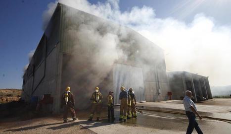 Bombers, ahir, treballant en l'extinció de l'incendi de la nau d'Alcarràs.