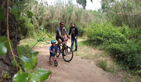 Una família amb bicicleta al Parc de la Mitjana de Lleida el mes de juny passat.