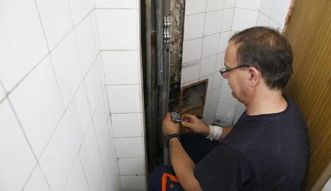 Un operari reparant ahir la canonada que va rebentar de l'edifici dels sindicats.