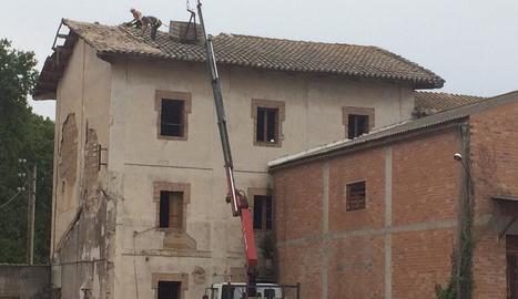 Operaris han començat a treballar a la teulada amb l'ajuda d'una grua.