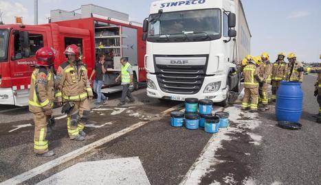 Els bombers van retirar amb cubells el combustible del camió després de l'accident a Ribera d'Ondara.