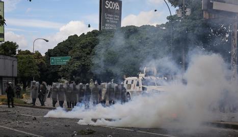 Enfrontament entre manifestants i policia, ahir a Caracas, durant la marxa de suport a jutges.