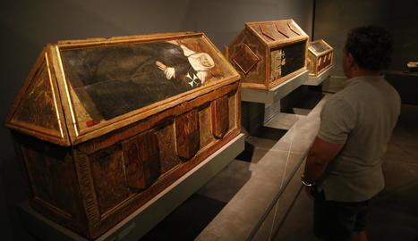 Un visitant contemplant les tres caixes sepulcrals del Museu de Lleida reclamades per Aragó.