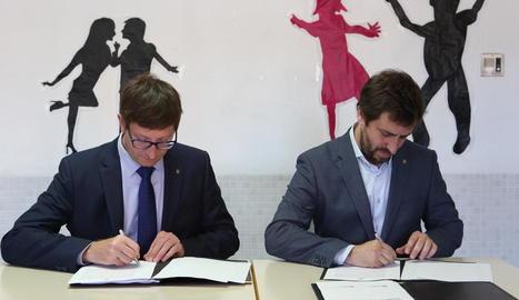Els consellers Mundó i Comín, ahir durant la firma del conveni.
