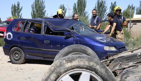 Bombers professionals mostren als aspirants un exercici d'excarceració en un vehicle al parc de bombers de Lleida.
