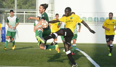 El centrecampista del Lleida Mustapha refusa la pilota davant d'un jugador del Cerdanyola.