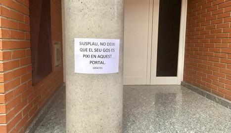 Cartell a l'entrada d'un bloc de pisos al carrer Bellpuig.