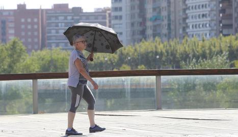 Una dona es protegeix del sol amb un paraigua, ahir, per creuar la passarel·la sobre el riu Segre.