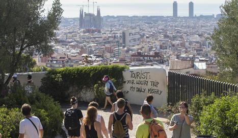 Imatge d'una pintada contra el turisme massiu al parc Güell.