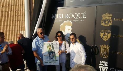 Els seus pares, amb el cartell de l'homenatge davant la porta 2-22.