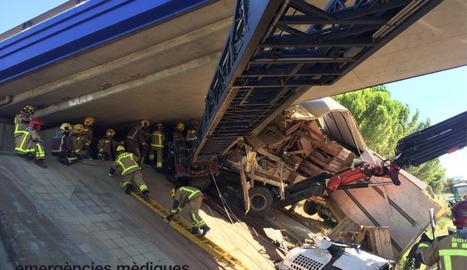 Una imatge de l'accident, amb els serveis d'emergència treballant per excarcerar el camioner.