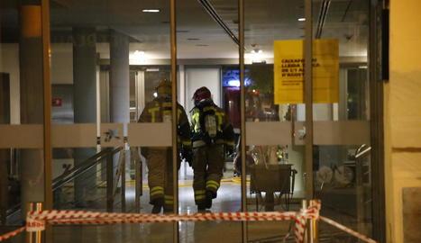 Dos bombers, ahir a la nit, a l'interior del CaixaForum poc després que comencés l'incendi.