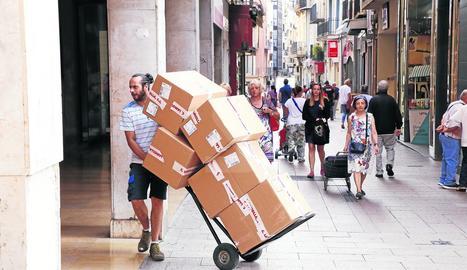 Un repartidor, com molts altres aquest dimarts, porta caixes en un carretó per repartir-les per les botigues.
