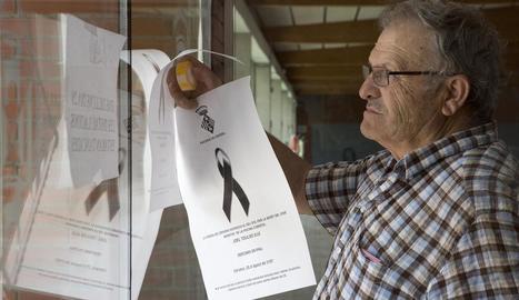 El regidor Josep Ortiz penjant cartells en què s'informava del tancament en senyal de dol.