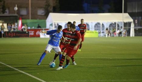 Un futbolista de l'Alcarràs controla la pilota davant de dos rivals.