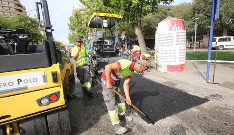Operaris encarregats de l'obra pavimentant una parada d'autobús a Prat de la Riba.