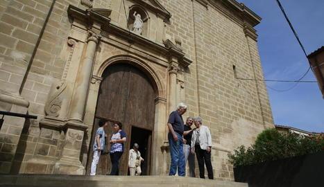 Feligresos de Benavent a la sortida de l'església, la façana de la qual presideix la controvertida escultura.