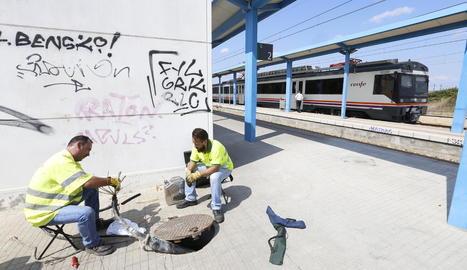 Operaris d'Adif a l'estació de Puigverd de Lleida mentre el tren efectua la parada.